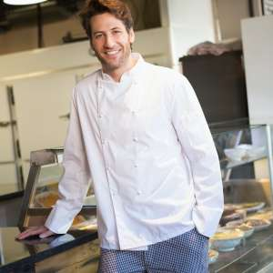 smiling-baker-leaning-on-counter-at-the-bakery.jpg